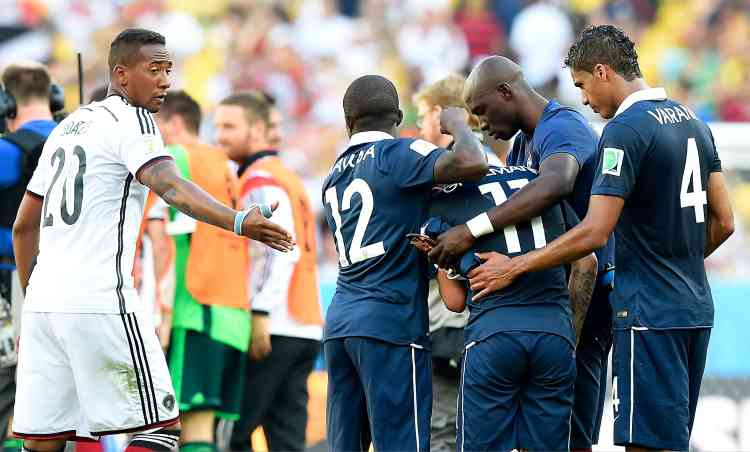 Germany's defender Jerome Boateng (L) holds out his hand towards France's midfielder Rio Mavuba as France's team react after losing the quarter-final football match between France and Germany 1-0 at the Maracana Stadium in Rio de Janeiro during the 2014 FIFA World Cup on July 4, 2014.  AFP PHOTO / FRANCK FIFE