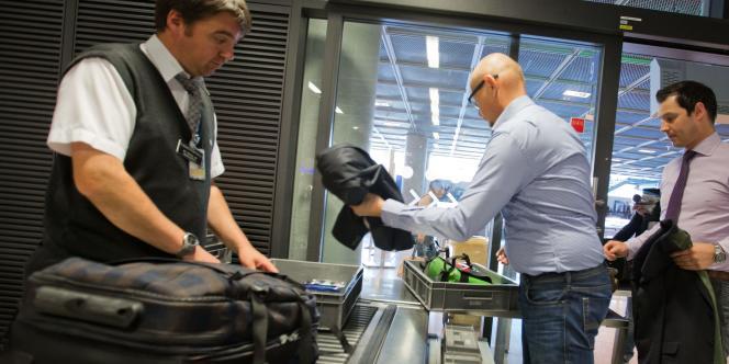 Des passagers refont leurs bagages après un contrôle de sécurité.