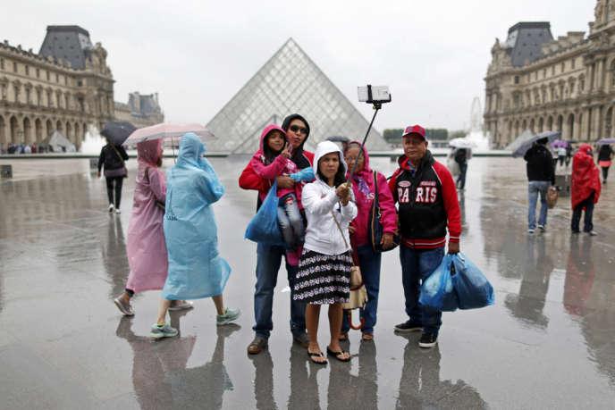 Des touristes font un selfie près de la pyramide du Louvre, à Paris, le 9 juillet.