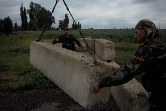 Des combattants prorusses construisent un point de contrôle à l'entrée du village de Marïnka, près de Donetsk, mardi 8 juillet.