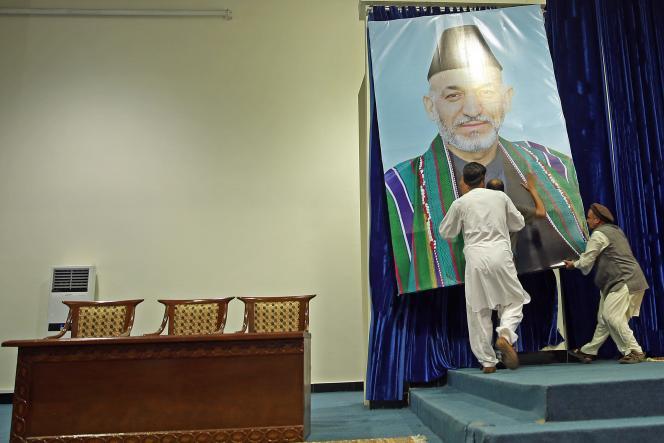 Des partisans du candidat Abdullah Abdullah décrochent une affiche du président sortant Hamid Karzaï avant un meeting, le 8 juillet à Kaboul.