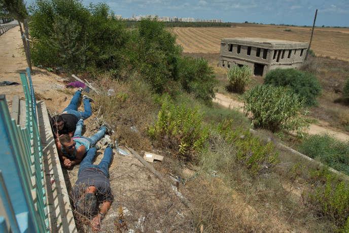 Des hommes se mettent à l'abri d'un tir de roquette palestinien, dimanche 13 juillet à Ashkelon (sud d'Israël).