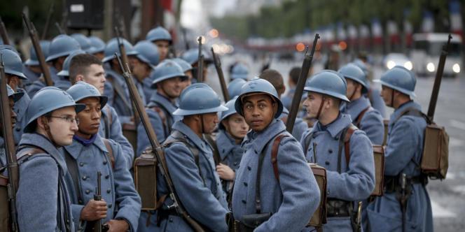 Des jeunes habillés en poilus de la guerre 14-18 attendent de défiler sur les Champs-Élysées, à Paris, le 14 juillet.