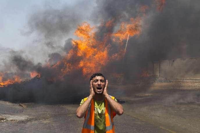 Un pompier palestinien devant un entrepôt en feu, le 12 juillet à Gaza.