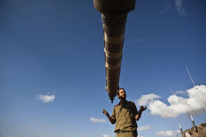 Un soldat israélien devant un tank aux alentours de Gaza, le 14 juillet.