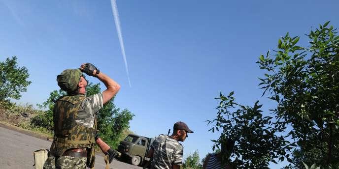Des militants prorusses regardent passer un avion de l'armée ukrainienne, à Marynivka, à 100kilomètres à l'est de Donetsk.