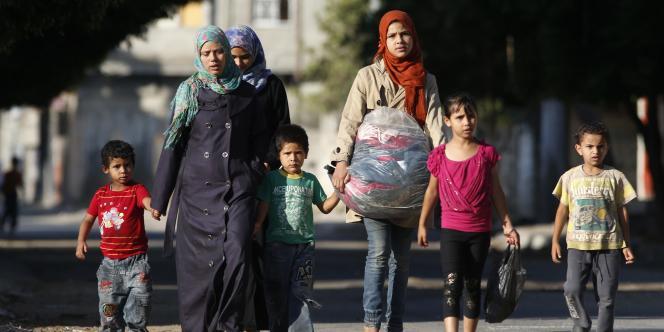 Des Palestiniens fuient leur maison après avoir reçu des tracts israéliens demandant d'évacuer le quartier de Zeitoun à Gaza.