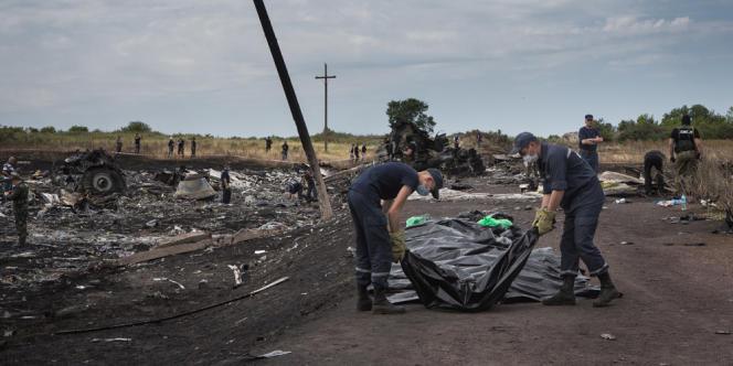 Des secours ukrainiens portent le corps d'une victime, tandis que les séparatistes prorusses gardent le lieu du crash, près du village de Hrabove, en Ukraine.