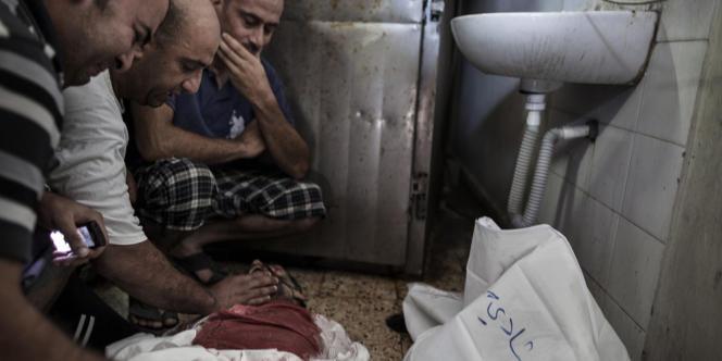 Des Palestiniens couvrent le corps d'un membre de leur famille tué par l'armée israélienne, dans la ville de Gaza, le 20 juillet. Plus de 100 Palestiniens sont morts suite aux attaques israéliennes le 20 juillet.