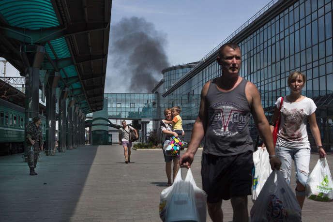 Des habitants se déplacent vers la gare de Donetsk, en Ukraine. Au second plan, la fumée s'échappe d'une ancienne usine de voiture touchée par un missile Grad.