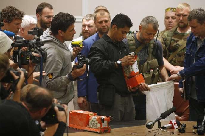 Remise des boîtes noires du vol MH17 de la Malaysia Airlines à des experts malaisiens par le chef des séparatistes pro-russes, Alexandre Borodaï (au second rang, en veste bleue), mardi 22 juillet, à Donetsk.