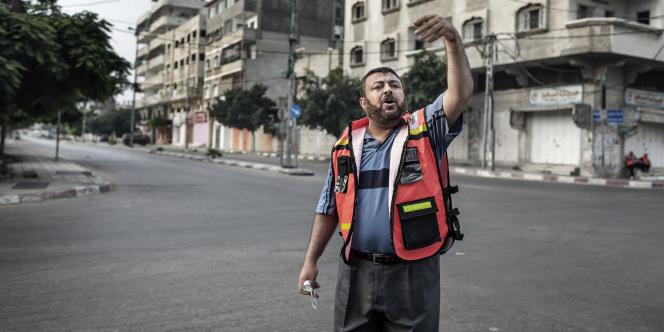 Un Palestinien de la Croix-Rouge fait évacuer les gens alors qu'un drone israélien signale le lancement d'un missile par l'armée, dans la ville de Gaza, le 22juillet.