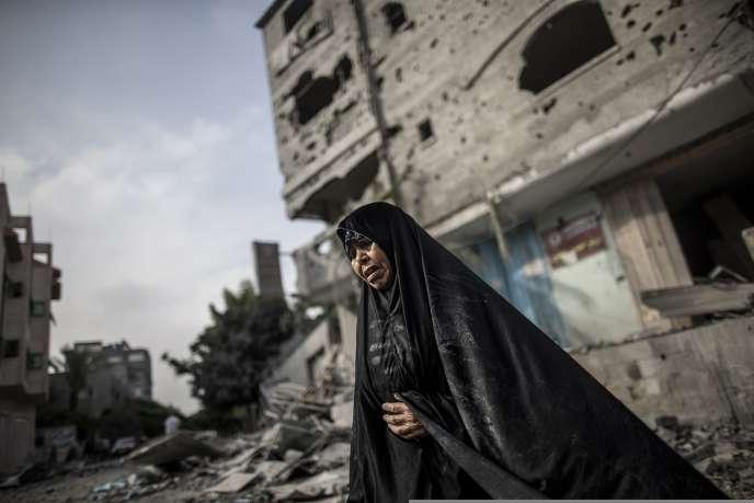 Une Palestinienne aux abords d'immeubles bombardés par l'armée israélienne, dans le nord de la bande de Gaza, le 24 juillet.