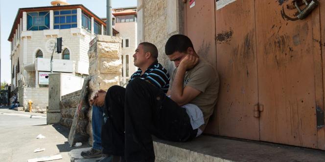 Yusuf Abou Khdeir, à gauche, est assis avec son ami à l'endroit où son neveu Mohammed a été kidnappé avant d'être assassiné, à Jérusalem-Est, dans le quartier de Chouafat.