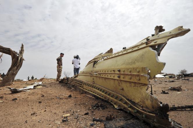 Un soldat français et un journaliste devant les débris du vol d'Air Algérie, samedi 26 juillet.