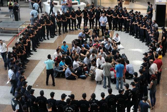 Des policiers entourent d'anciens collègues arrêtés pour