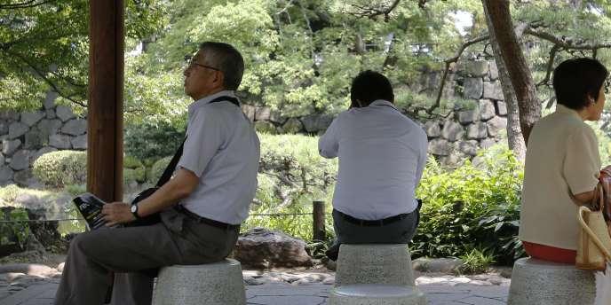 Des Japonais s'abritent du soleil dans un parc de Tokyo, le 15 juillet.