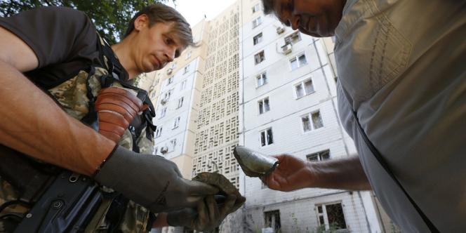 Des séparatistes pro-russes observent des fragments de munitions à Donetsk, le 29 juillet 2014.