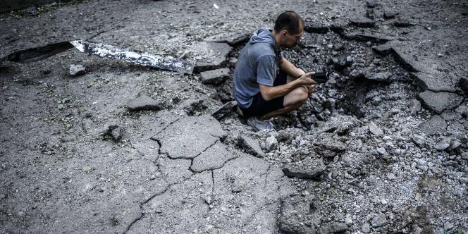 Un homme filme un trou d'obus, le 29 juillet 2014, à Donetsk.