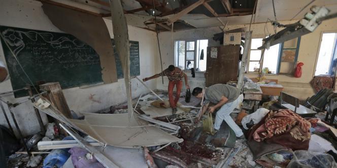 Des Palestiniens recueillent des restes des corps des 16 enfants réfugiés dans l'école de l'ONU de Jabalia et tués, mercredi 30 juillet 2014, par des tirs de chars israéliens.