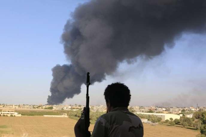 Un combattant de Zintan surveille, le 2 août, le panache de fumée qui s'échappe d'un réservoir de carburant en feu près de l'aéroport de Tripoli.