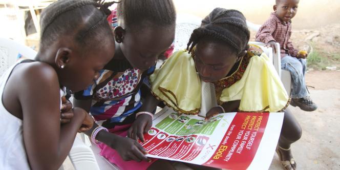 Des fillettes libériennes consultent un document de prévention sur le virus Ebola.
