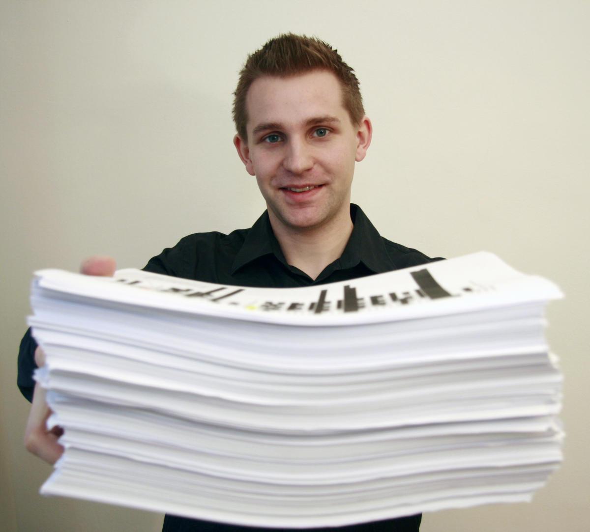 Maximilian Schrems pose avec les 1 200 pages d'informations collectées sur lui par Facebook.