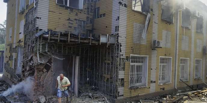 Un homme fuit un immeuble détruit par les bombardements de l'armée ukrainienne, le 10août.