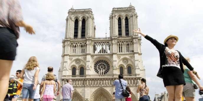 Des touristes devant la cathédrale Notre-Dame, à Paris, en août.