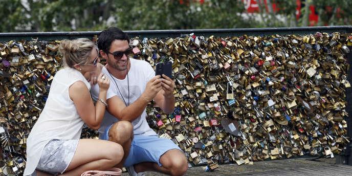 Un couple se prend en photo devant des cadenas au pont des Arts, à Paris, en 2013.