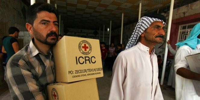 Des Irakiens déplacés par l'avancée des djihadistes de l'Etat islamique reçoivent de l'aide de la Croix-rouge internationale, le 5 août à Najaf.
