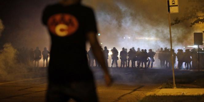 Un manifestant fait face aux forces de l'ordre à Ferguson dans la banlieue de Saint-Louis (Missouri) lors de la quatrième nuit de violences qui secouent la ville depuis la mort de Michael Brown, le 9 août 2014.