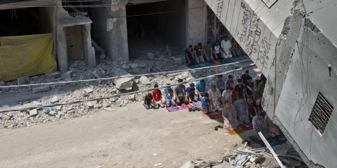 A Gaza, des hommes prient sous le minaret détruit d'une mosquée, le 15 août.