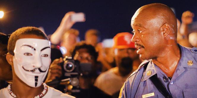 Le capitaine Johnson, responsable du maintien de l'ordre à Ferguson, aux côtés d'un manifestant arborant le masque de Guy Fawkes, emblème des Anonymous.