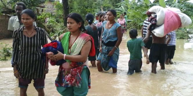 Des Népalais tentant d'échapper aux inondations, le 15 août.
