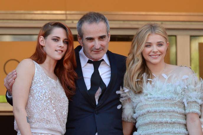 Le réalisateur Olivier Assayas entouré des actrices Kristen Stewart (à gauche) et Chloë Grace Moretz lors du 67e Festival de Cannes, le 23 mai 2014.