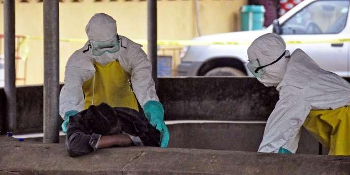 Deux soignants bougent le corps d'un homme mort probablement d'Ebola, le 16 août 2014 à Monrovia, capitale du Liberia.