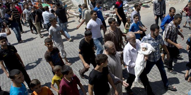 Le père de Wadad Al-Asfour porte la dépouille de son petit-fils, tué par une attaque d'Israël qui visait Mohammed Deif.