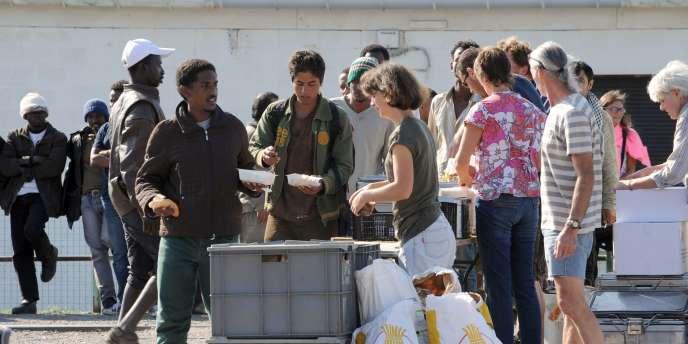 Les membres d'une ONG distribuant de la nourriture aux migrants à Calais, le 5 août.