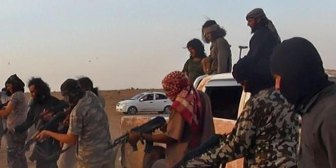 Détail d'une image publiée par l'EI montrant des hommes masqués membres de l'Etat islamique s'apprêtant à exécuter des hommes après la prise de la base aérienne de Taqba.
