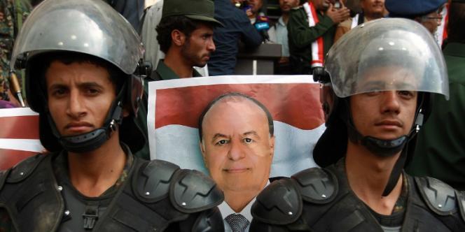Les forces de sécurité yéménites devant un poster du président Abd Rabbo Mansour Hadi lors d'une manifestation progouvernement le 26août2014 à Sanaa, capitale du Yémen.