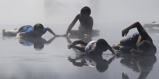 Des enfants jouent dans une fontaine à Nice, lors d'une journée très chaude, le 18 juillet 2014.
