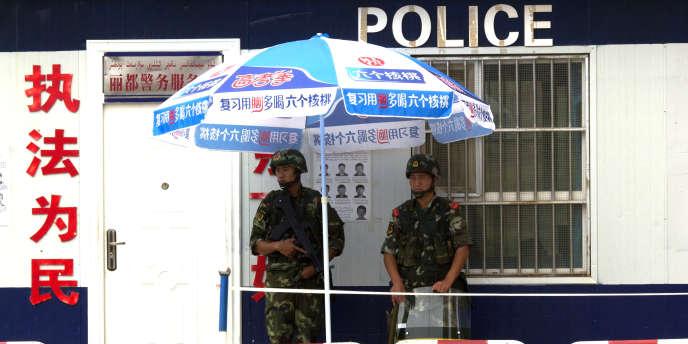 Des soldats chinois aux abords d'un point de contrôle à Aksu, dans la province chinoise du Xinjiang, en juillet 2014.