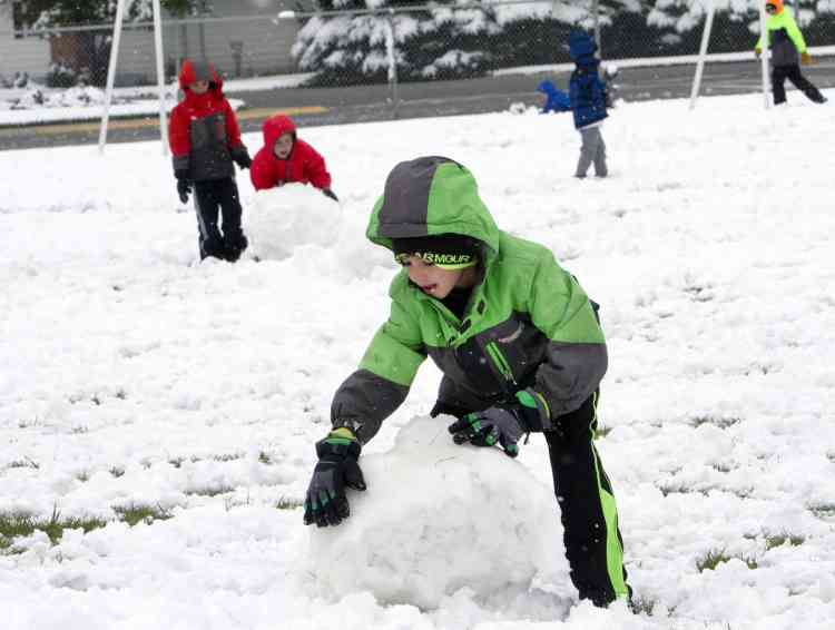 In this Thursday, Sept. 11, 2014 photo, Livingston Elementary second-grader Carter Thompson enjoys playing in the snow with classmates during recess in Cody, Wyo. A late summer snowstorm dropped 3 to 5 inches in Cody, the earliest recorded snowfall there since records were kept in 1915. Other parts of the state received up to 20 inches of snow. (AP Photo/The Cody Enterprise, Raymond Hillegas) POWELL TRIBUNE OUT