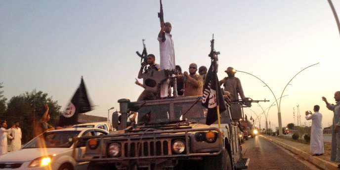 Des combattants de l'Etat islamique paradent à Mossoul, en Irak, le 23 juin.