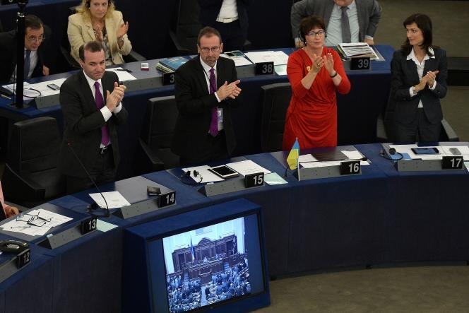 Les eurodéputés applaudissent, mardi 16 septembre à Strasbourg, le vote de l'accord d'association avec l'Ukraine. PATRICK HERTZOG/AFP