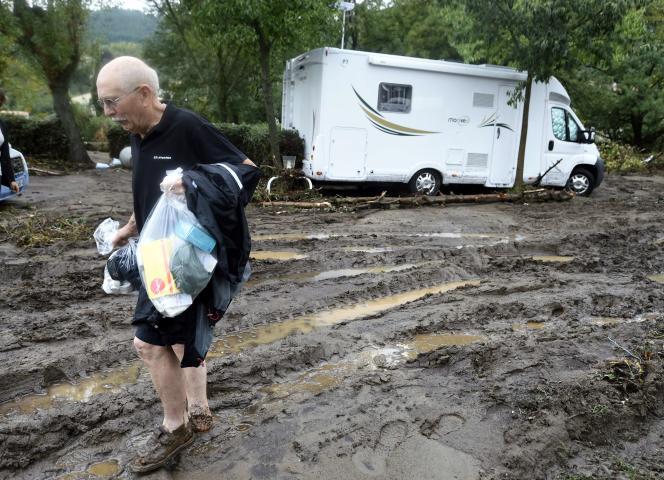 Un homme portant ses rares effets préservés lors de l'évacuation du camping municipal de Lamalou-les-Bains, le18septembre.