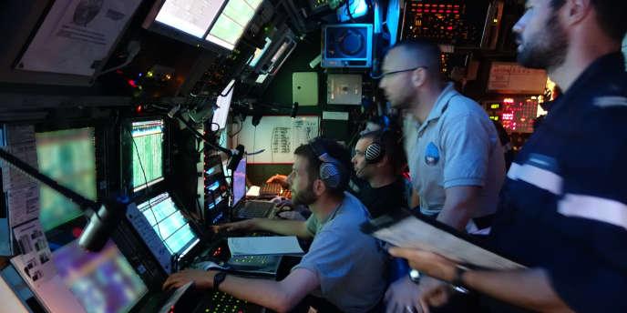 L'analyste de la « Perle » (au fond, en tee-shirt noir), devant les écrans sonar du poste de commandement des opérations.