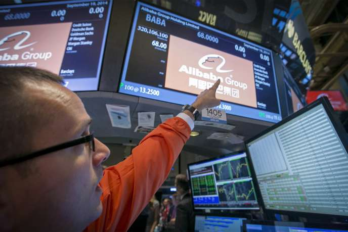 Specialist Trader Neil Gallagher points to the ticker symbol for Alibaba Group Holding Ltd during the company's initial public offering (IPO) under the ticker