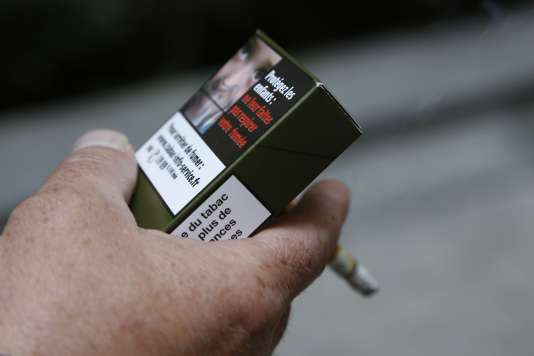 Un homme tenant un paquet de cigarettes neutre.